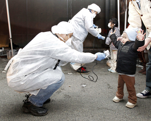 Image: File photo of officials in protective gear checking for signs of radiation in Koriyama
